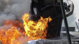 A vehicle burns at the scene of a bomb attack in Baghdad's Khadamiyah district on 15 August, 2013