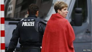 A woman covered in a blanket is escorted from the scene by police after the conclusion of a hostage situation in Ingolstadt (19 August 2013)