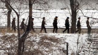 North Korean soldiers patrol along the Yalu River at the North Korean town of Sinuiju on 12 February 2013