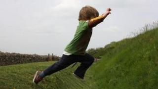 A young boy jumping over a grassy ditch