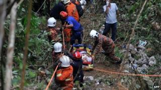 Malaysian emergency services personnel rescue a passenger (C) after a bus carrying tourists and local residents fell into a ravine near the Genting Highlands, about an hour's drive from Kuala Lumpur on August 21, 2013