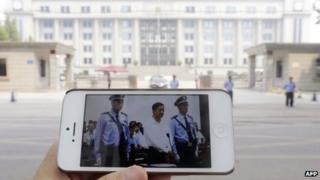 A mobile phone held by the photographer shows a photo from a court's microblog page of disgraced Chinese politician Bo Xilai standing trial in Jinan on 22 August 2013