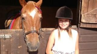 Ellie Harris standing next to a horse