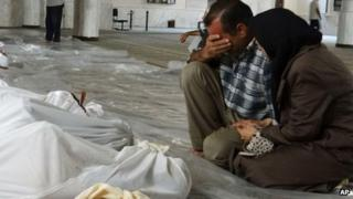 Mourners next to bodies of alleged chemical attack victims in Ghouta, Syria on Wednesday, 21 August 2013