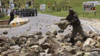 A protester drops a stone on a road in La Calera, near the capital Bogota on 23 August 2013