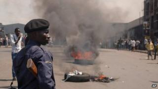 A police officer looks on as protestors burn tires in the street following recent violence, including mortar attacks that have struck homes and churches in the eastern provincial capital, killing at least seven civilians and wounding dozens of others, in Goma, Congo, Saturday, Aug. 24, 2013.