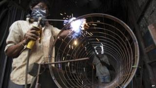 An Indian man works at a welding workshop in Ahmedabad, India, Thursday, Aug. 22, 2013