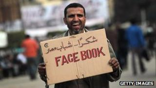 Protestor with a Facebook sign