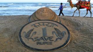 An Indian walks past a sand sculpture of a rupee coin on a beach in Puri, India, on 22 August