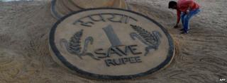 A rupee coin sketched in sand