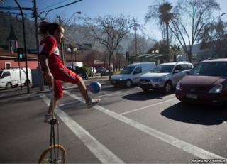 Cristian Rubio Munoz juggling while on a unicycle in front of halted traffic