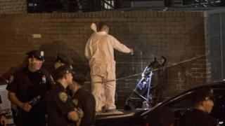 In this 1 September 2013 photo, police investigate the scene where a one-year-old was fatally shot early on Sunday night in the Brownsville area of Brooklyn, New York