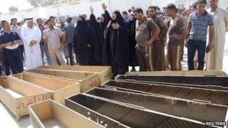 Women react near empty coffins as they wait to claim the bodies of their relatives, outside a hospital morgue in Mahmudiya, 30 km (19 miles) south of Baghdad, on 4 September 2013