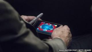 US Senator John McCain plays poker on his iPhone