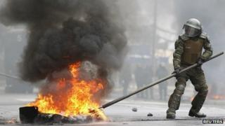 A riot police officer tries to extinguish burning tyres during a protest marking the military coup. September 4, 2013