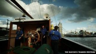 Tom Cook stands at the helm of the boat