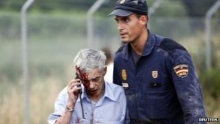 Francisco Jose Garzon helped away by policeman. 24 July 2013
