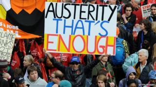"A man holds a sign saying ""Austerity that's enough"""