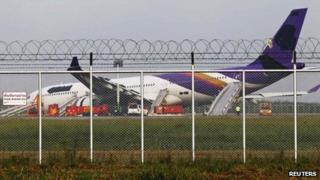 Airport staff work around a Thai Airways plane that skidded off the runaway while landing at Bangkok's Suvarnabhumi Airport on 9 September 2013