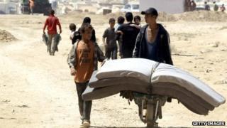 Boys carry mattresses through Zaatari refugee camp