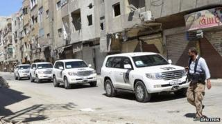 A Free Syrian Army fighter passes by the convoy of UN inspectors on 28 August