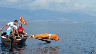 Bulgarian Jane Petkov tied up in a bag jumps in Lake Ohrid. Photo: 10 September 2013