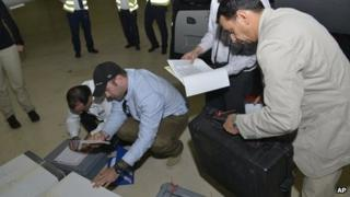 In this photo released 31 August 2013 by the Organization for the Prohibition of Chemical Weapons, samples brought back from Syria by the UN chemical weapons inspection team are checked in upon their arrival at The Hague, Netherlands