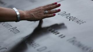 A attendee touches the stone with names of the 9/11 victims at the 9/11 Memorial during ceremonies marking the 12th anniversary of the 9/11 attacks on the World Trade Center in New York 11 September 2013