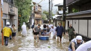 Hotel guests get a boat ride through a flooded street after the Katsura river was overflooded by torrential rains caused by a powerful typhoon in the country's popular tourist destination of Kyoto, western Japan, Monday, 16 September 2013