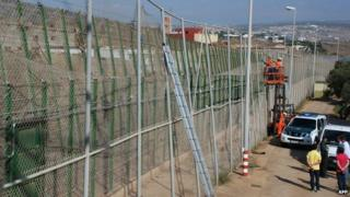 A handout picture taken and released on 17 September, 2013 by the Melilla's regional government shows employees repairing a border fence after immigrants tore it down to break from Morocco into Spain.