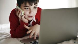 A boy with a laptop and a smartphone