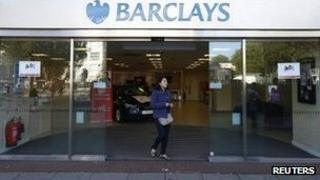 A woman leaves the Swiss Cottage branch of Barclays in north London