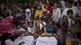 Sunday, Sept. 22, 2013: Peshawar, Pakistan_Pakistani women grieve over the coffins of their relatives, who were killed in a suicide attack on a church.