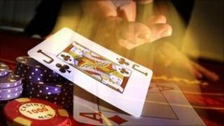 A hand and a card at a poker table