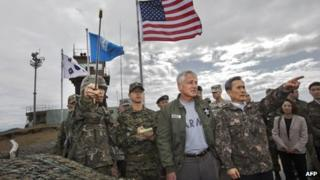 South Korean Defence Minister Kim Kwan-jin (right) points out a location in North Korea to US Secretary of Defence Chuck Hagel from Observation Point Ouellette during a tour of the Demilitarized Zone (DMZ), the military border separating the two Koreas, in Panmunjom, South Korea, on 30 September 2013