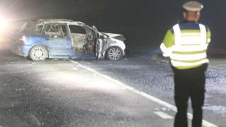 Police officer standing near car which has been destroyed by fire