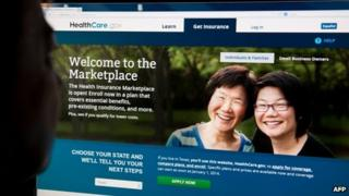 A woman looks at the HealthCare.gov website on 1 October 2013