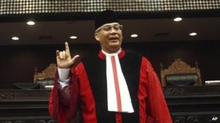 In this 20 August 2013 photo, Indonesia's top judge Akil Mochtar poses for photos during a swearing-in ceremony in Jakarta