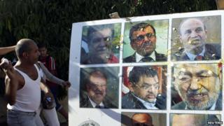 An anti-government protester throws an egg at a poster of Tunisian politicians, including Prime Minister Ali Larayedh (top row, C) and leader of the Islamist Ennahda movement Rached Ghannouchi (centre row, R) during a demonstration in Tunis, 2 October, 2013.