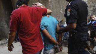 Man is detained by Egyptian security forces during operation against Islamist stronghold in Giza's Kerdasa district, south of Cairo, on 26 September 2013