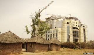 Old-style homes with straw roofs next to new building under construction in Abuja