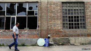 """A worker passes by an abandoned production hall at the """"Zastava Arms"""" weapons factory in the Serbian town of Kragujevac"""