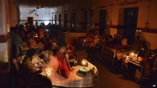 In this Monday, Oct. 7, 2013 photograph, patients light candles and use hand fans to beat humidity at the King George hospital during a power outage at Visakhapatnam, Andhra Pradesh state, India. W