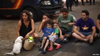 Carolina Gonzalez (L) and her three- and four-year-old children sit in a street with activists after riot police evicted them from an unoccupied building in Malaga, southern Spain, 3 October