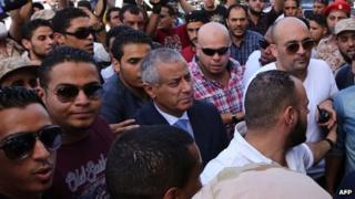 Libyan PM Ali Zeidan (centre) following his release by militiamen in Tripoli on 10 October 2013