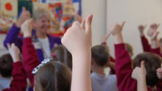 Primary pupils give thumbs up in classroom