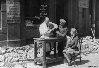 """A vet treats a dog outside after his premises are blown out by a bomb. A sign reads: """"Animals humanely destroyed"""""""