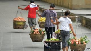 Vendors carrying food items in China
