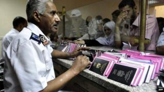 Egyptian custom officials check passports and identity cards as travellers wait on Egyptian side of the Rafah border crossing point on 10 August 2012