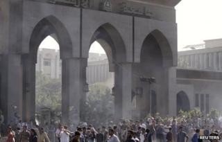 Protesters gather amidst remnants of tear gas during clashes with police at Al-Azhar University in Cairo